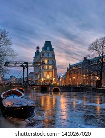 Frozen canal in Amsterdam with boat, bridge and beautiful illuminated building in the winter
