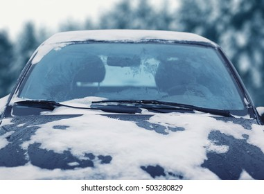 Frozen car covered snow in winter day, view windshield hood