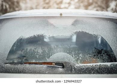 Frozen car, rear window and cleaner in winter.