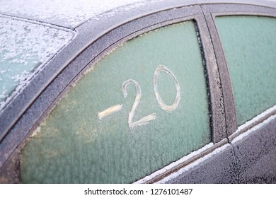 "Frozen car window with scratched text on the ice: ""-20"" (minus twenty)"