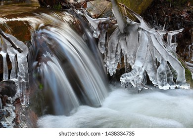 Frozen cascade of waterfall icy twigs and icy boulders in frozen foam of rapid stream. Winter creek. Extreme freeze.