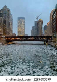 A frozen Chicago River with cracked ice chunks during frigid January evening commute in winter