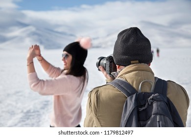 Frozen Cildir Lake in Kars - January 2018: The man is taking photos of the girl while she is making heart by her hands and fingers on frozen Cildir Lake in Kars.