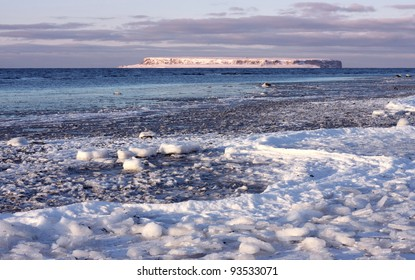 Frozen coastal landscape with island outside.