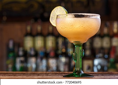 Frozen cocktail Margarita, a classic recipe. Given in a glass with a salted rim and slice of lime. Space for text