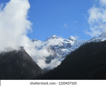 Frozen cold mountains. Top peak of Kanchenjunga. Beautiful snow and landscape with blue cloudy sky. Alpine forest surrounding.