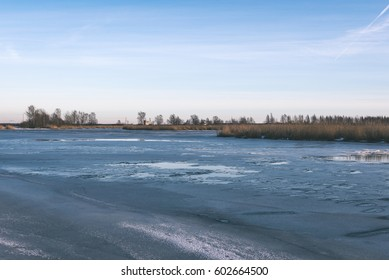 frozen countryside scene in winter with snow. iced river with blocks of ice