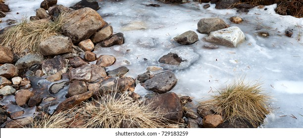 Frozen creek with stepping stones across the ice. Banner format