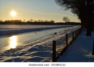 A frozen Dutch canal and footpath silhouetted by a winter sunset