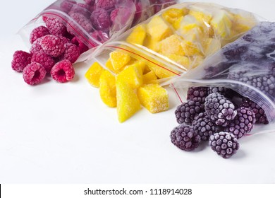Frozen ecological berries in reusable plastic bags: raspberry, mango and blackberry. White background