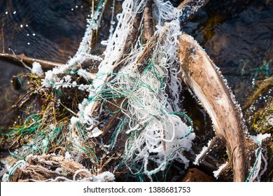 Frozen ejected net for fishing hangs on the snag in river
