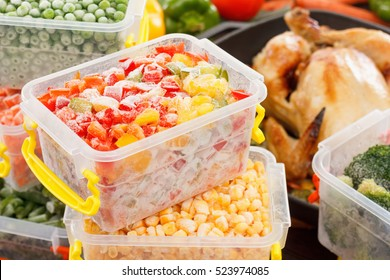 Frozen foods vegetables cook in plastic containers, fried chicken in pan. Healthy freezer meals.