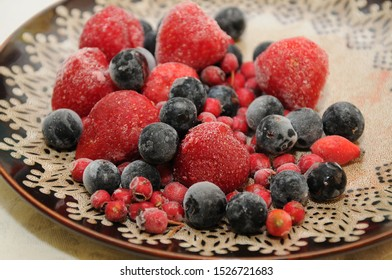 frozen forest fruits strawberry  blueberry on a plate in a group