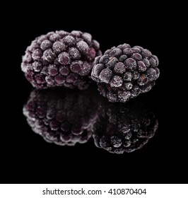 frozen fruit - blackberry with small ice crystals on black mirror