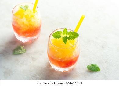 Frozen Granita Wine Slush Drink on rustic stone table. Homemade Italian Granita Dessert, refreshing  summer Gradient Tropical Slush Drink with mint.