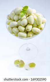 Frozen green grape in martini glass with peppermint .