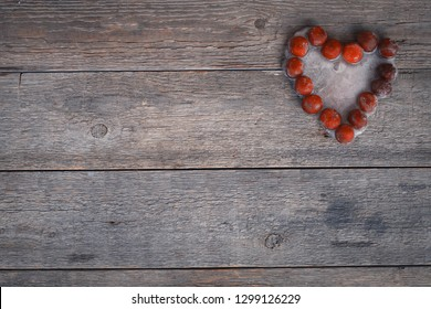 The frozen heart from cherry on an old wooden background. Concept of unrequited love