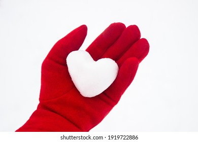 Frozen heart. A heart of snow in a woman's hand in a red glove. Callousness, indifference, coldness