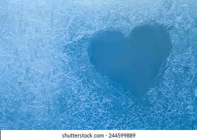 Frozen heart in window. Valentines day concept. Ice flowers macro view. Frost texture pattern. cold winter weather xmas background