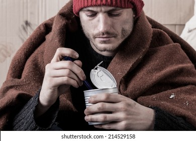 Frozen homeless man eat food from cans