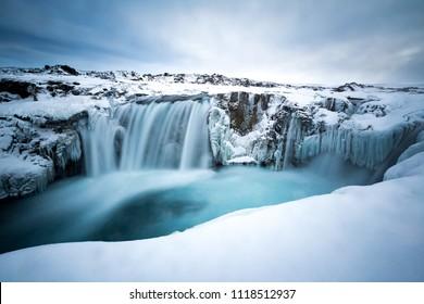 Frozen Hranabjargafoss waterfall during winter