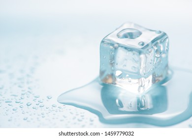 Frozen ice cube on blue background with empty space for text
