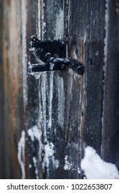 Frozen ice gate latch on wooden barn door. Icicles and ice formations. Cold winter scene. Bad weather. Canada