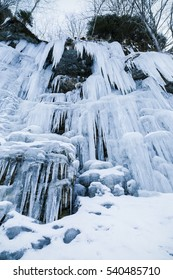 Frozen icicles on rocky wall at the mountain, closeup with selective focus