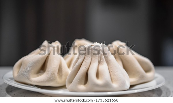 Frozen khinkalis on a plate ready to be boiled. Four uncooked khinkali ready to cook. Copy space. Side view.