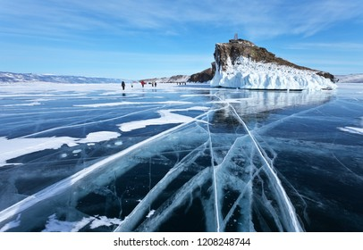 Frozen Lake Baikal. A group of tourists came on an excursion to the beautiful iced cape of Horin-Irgi or Cape Kobyliya Golova