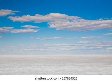 Frozen lake and blue sky with clouds. Winter landscape.