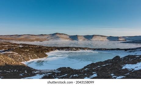 A frozen lake in the form of an ice heart. Snow lies on the ground, devoid of vegetation.  Nearby is Lake Baikal. A mountain range against the blue sky. Siberia