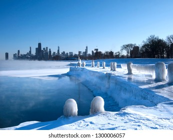 Frozen Lake Michigan with steam coming up and a frozen pier covered in ice during polar vortex and skyline view of Chicago.