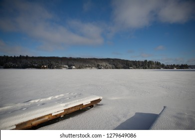 Frozen lake in Muskoka, Ontario Canada. The wooden dock covered in snow is visible. Across the lakes few cottages are nestled between trees.