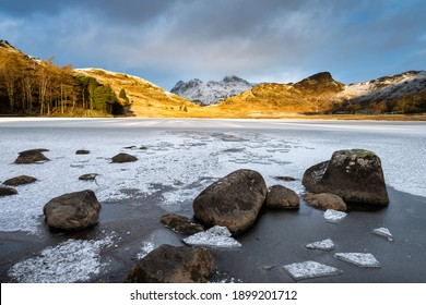 Frozen lake with rocks and ice on shoreline. View to snowcapped mountains with morning golden light. Blea Tarn,  Lake District, UK.
