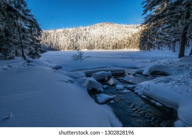 Frozen lake and small mountain river