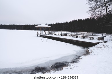 Frozen lake and snowy bridge on the shore.