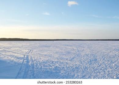 Frozen lake at sunny winter day, Leningrad region, Russia.
