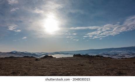 The frozen lake is surrounded by snow-capped mountains. The sun is shining in the blue sky.  Light clouds. In the foreground is dry land, devoid of vegetation. Baikal