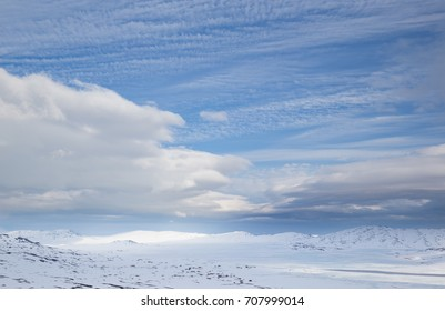 Frozen lake Vinstre and vast snow covered landscape with tiny red houses in Oppland, Norway