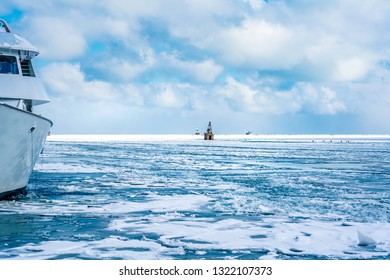 The frozen landscape of Lake Michigan in the winter, covered in layers of ice and snow, and a buoy frozen in the distance, and a boat frozen in place, shot from a pier in Chicago, Illinois, USA.