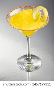 Frozen lemon margarita, salt and bird's beak dry chile rimmed in a cocktail glass with a slice of lemon and lots of frost