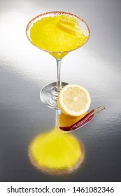 Frozen lemon margarita, salt and bird's beak dry chile rimmed in a cocktail glass with a twist of lemon, a bird's beak pepper, half a lemon and lots of frost
