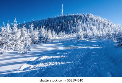 frozen Lysa hora hill in Moravskoslezske Beskydy mountains with hiking trail and clear sky during really cold winter day