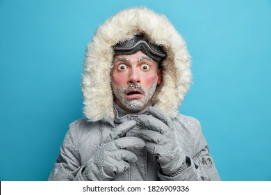 Frozen male explorer has red face covered with frost stares very shocked at camera surprised by very low temperature wears warm jacket and gloves has walk outdoor during blizzard cold weather
