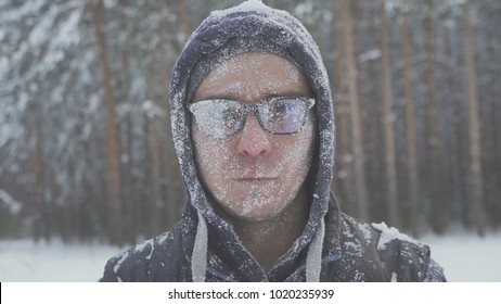 a frozen man with glasses in the snow looks at the camera in the winter forest after a snow storm
