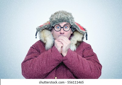 Frozen man in winter clothes and glasses warming hands, cold, snow, blizzard