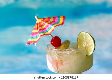 frozen margarita drinks with lime and cherry garnish and a colorful drink umbrella