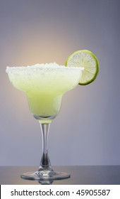 Frozen Margarita mixed drink with lime slice on plain background close up