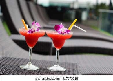 Frozen margarita with strawberry on wooden table